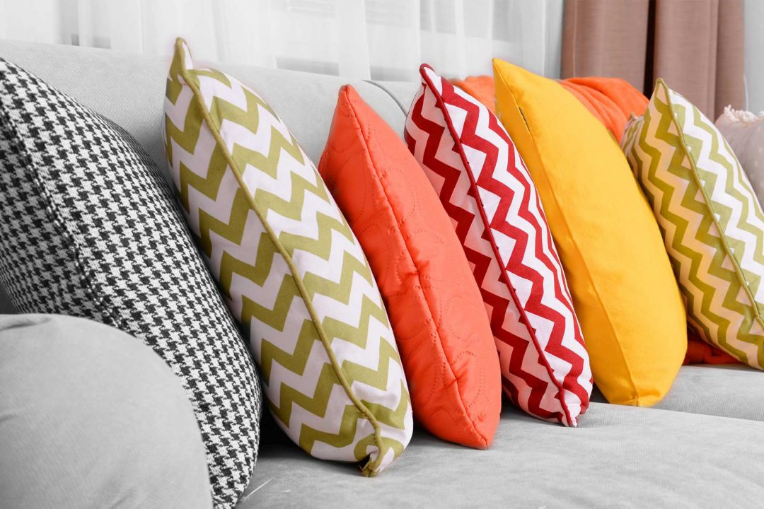 An image of workroom pillows in various colors placed on a couch